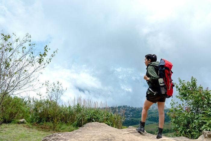 リュックを背負ってハイキングをしている女性の写真