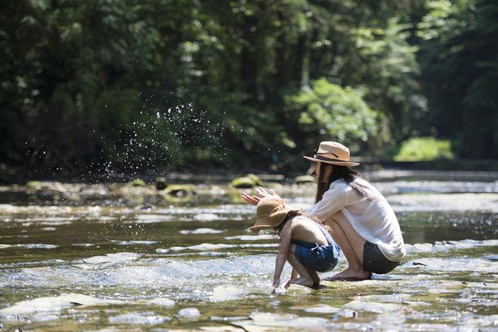 渓流で遊ぶ親子の写真