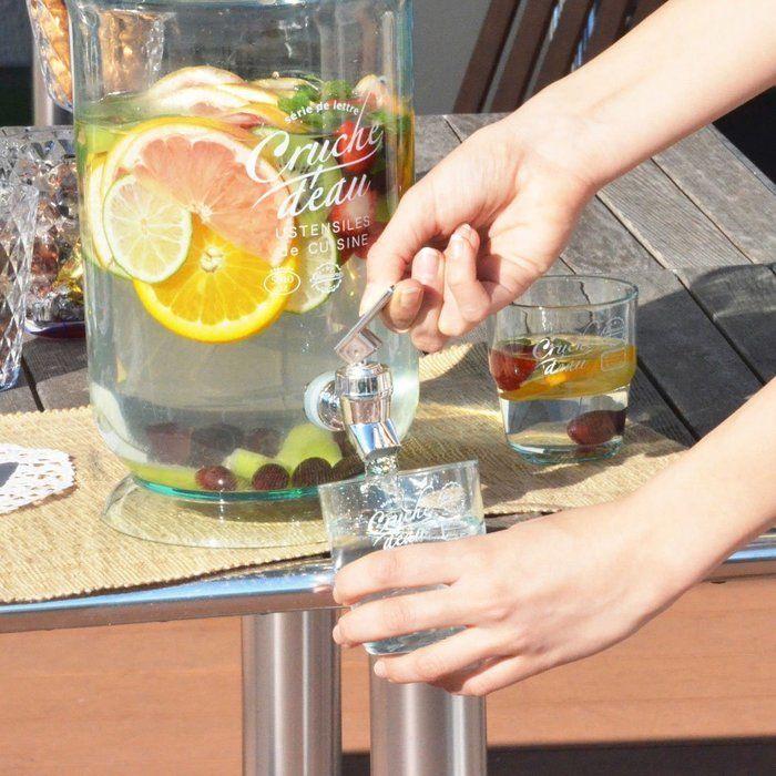 ジャグから水をコップに入れている画像