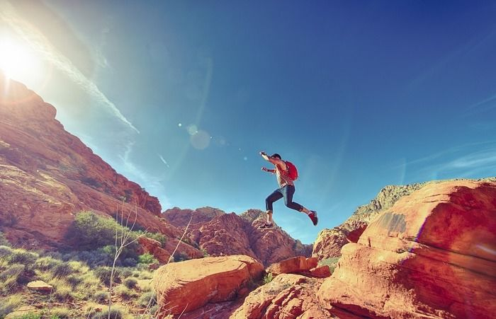 岩山を走って飛んでいる男性