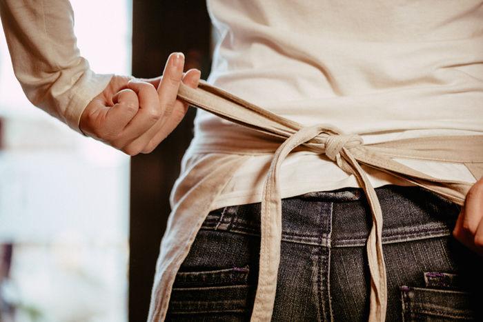 エプロンの紐を結んでいる写真