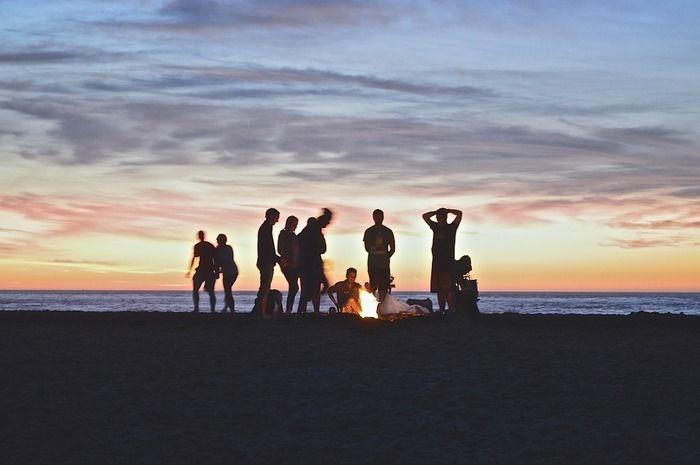 夕暮れの海に焚き火をしている青年達