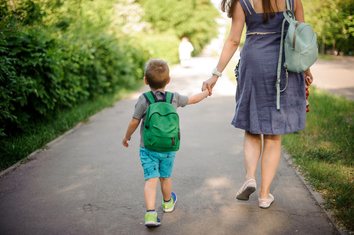 親子でリュックを背負って歩いている写真