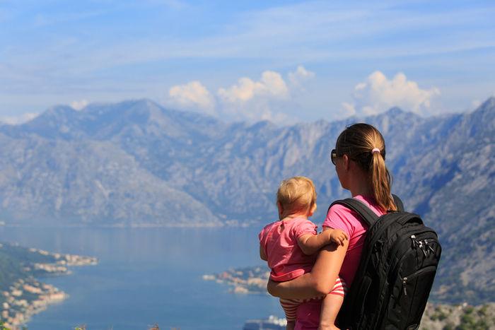 赤ちゃんを抱えながら山を見ている母親