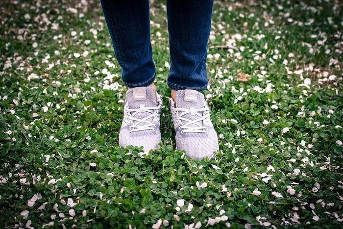 草の上にスニーカーを履いて立っている人