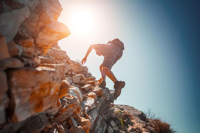 リュックを背負って岩を登っている男性