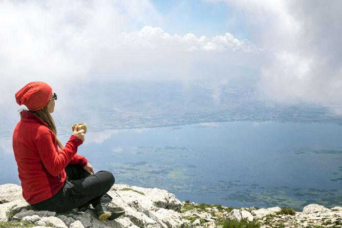 山の上で飲み物を飲んでいる女の人