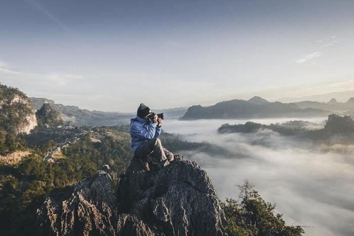 山頂からカメラで写真をとっている写真