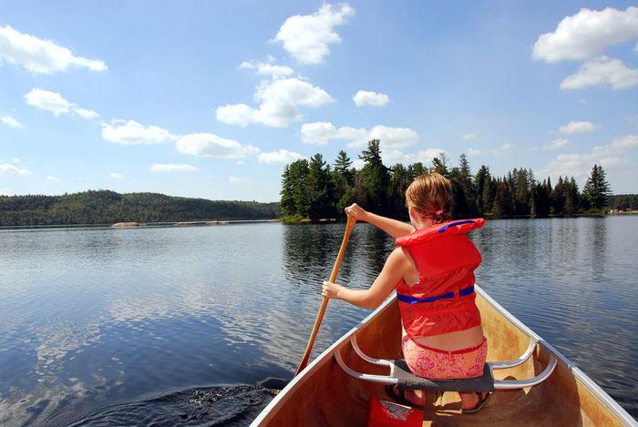 ベストを着てカヌーを漕いでいる女性