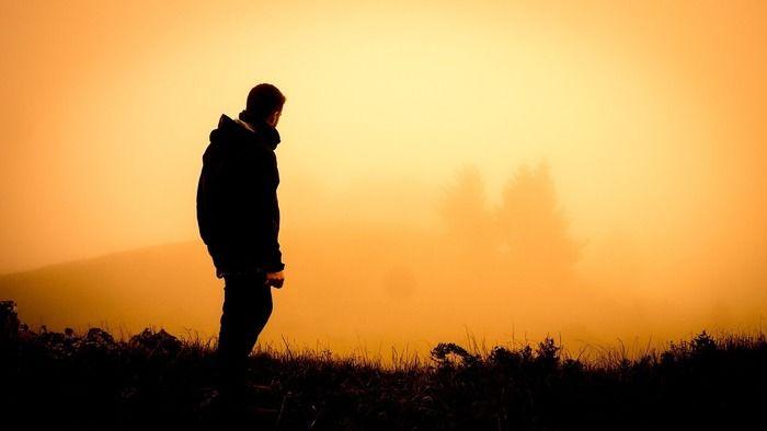 草原で夕日を見ている男性
