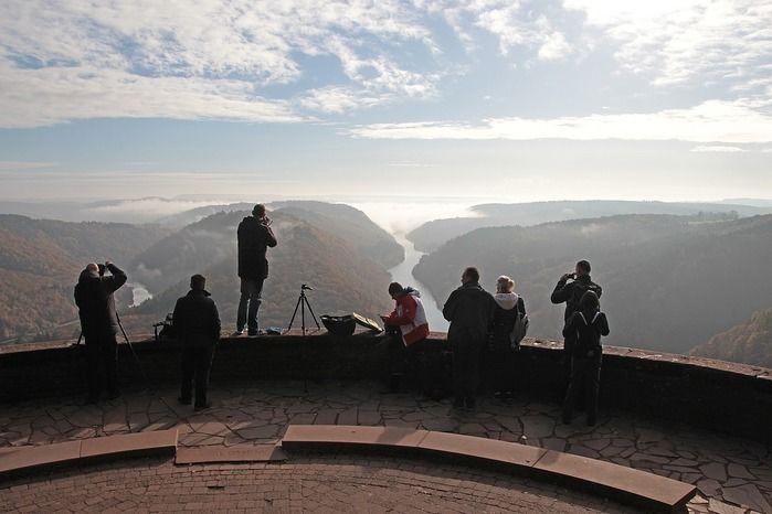高台からカメラで景色を撮影している人たち