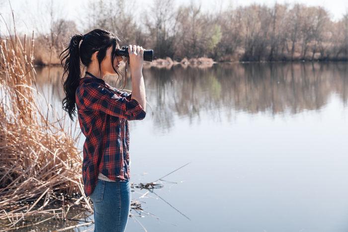 双眼鏡で湖を観察している女性
