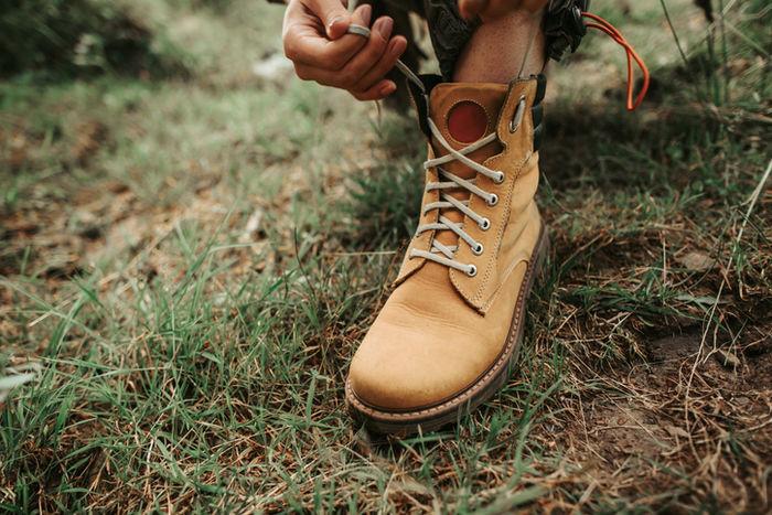 ワークブーツの靴紐を結んでいる写真