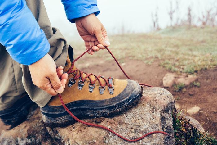 ワークブーツの靴紐を結んでいる様子