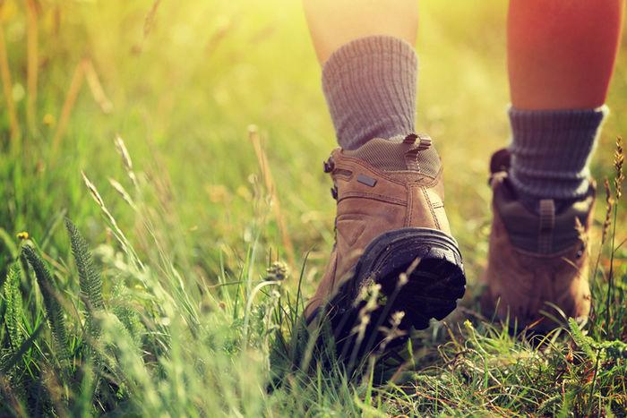 ブーツを履いて草むらを散歩している人の足元