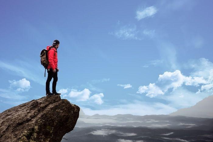 崖の先っぽで周りを見渡せしている男性