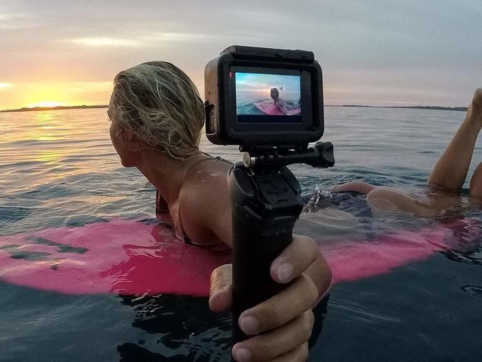 サーフィンしながらゴープロでセルフィーを取っている女性
