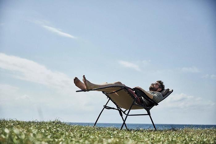 リラックスチェアで寝ている男性の写真