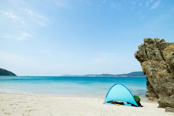 海の砂浜でテントが張ってある写真