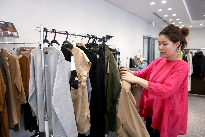店内で服を整理している女性の写真