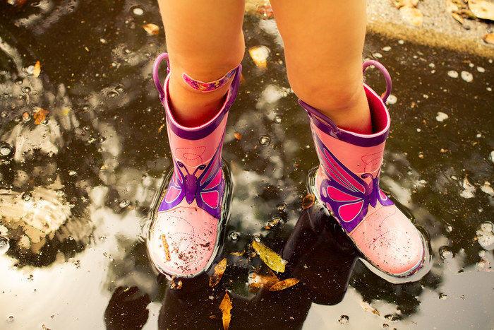 子供が長靴を履いて水溜まりに入っている写真