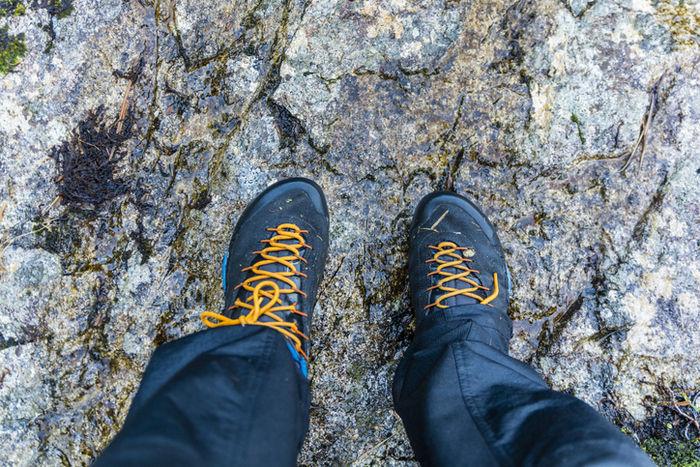岩の上に立っている防水靴を履いた人の足元の写真