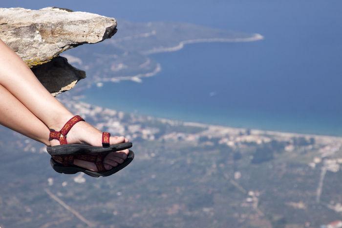 サンダルを履いて崖から足を出している女の人