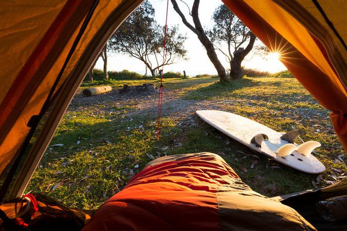 朝サーフィンをしてテントの寝袋に包まっている写真