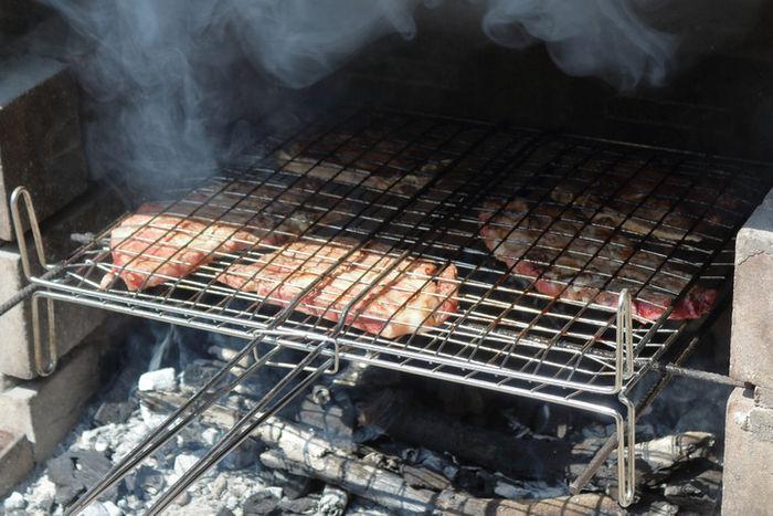 キャンプで肉を焼いている写真