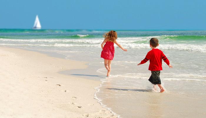 海で追いかけっこしている子供の写真