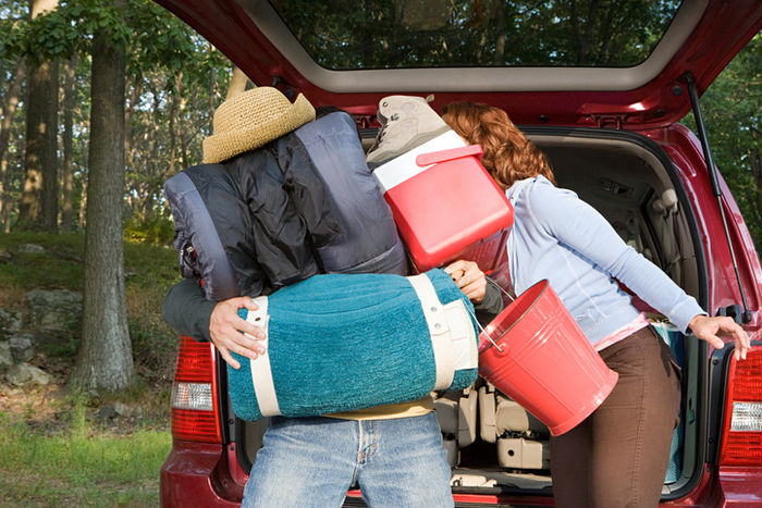 キャンプ道具を運んでいるカップルの写真