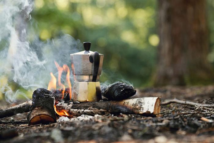 焚き火の火でお湯を沸かしている写真