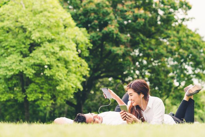 公園で寝そべる男女