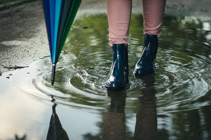 水たまりを歩く女性