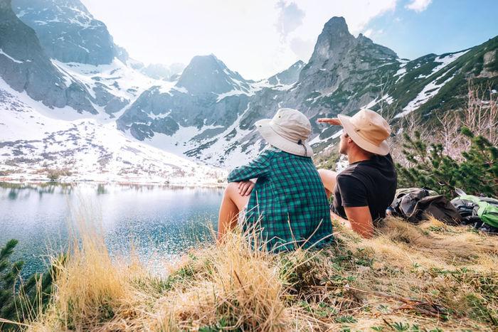 アウトドアハットを被って自然を見ているカップルの写真