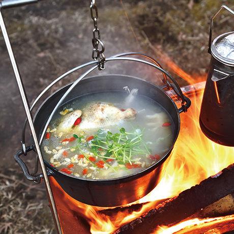 ユニフレームのダッチオーブンを焚き火で温めている写真
