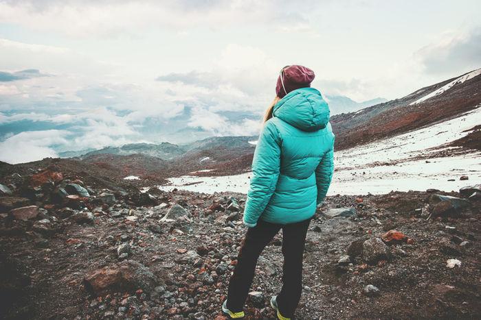 ダウンジャケットを着た女性が山頂に立っている写真