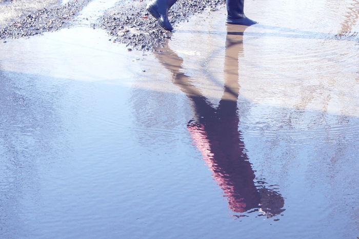 水溜まりに反射している人の写真