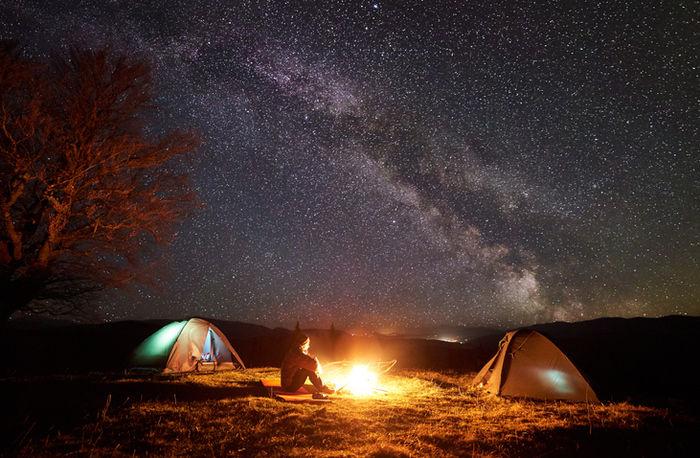 満点の星空の下でテントを貼って焚き火をしている様子の写真
