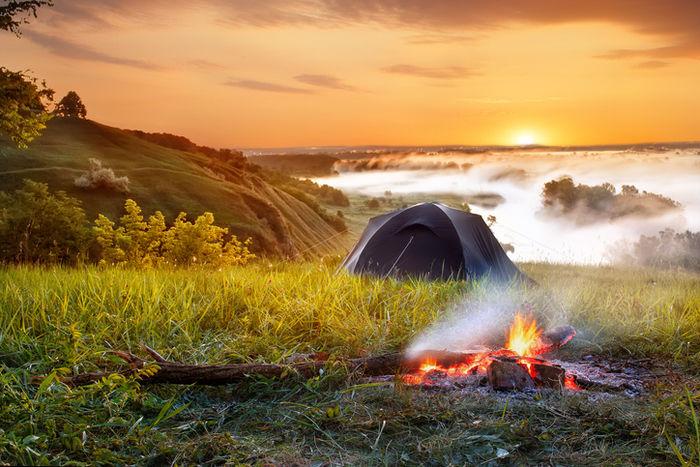 早朝にテントを貼っている山で焚き火をしている写真