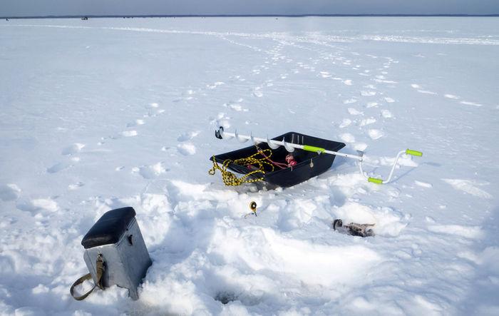 氷上に釣りの道具が置いてある写真