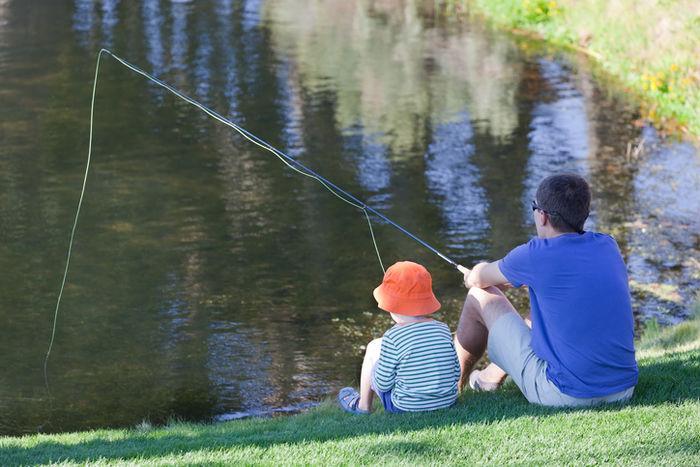 池で釣りをしている親子の写真