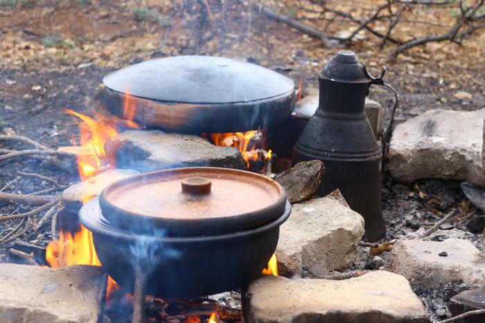 焚き火にかけているダッチオーブンの写真