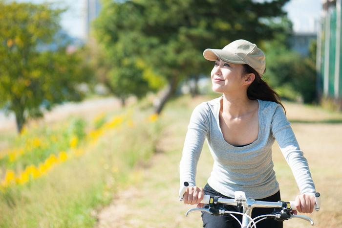 川沿いをサイクリングしている女性の写真