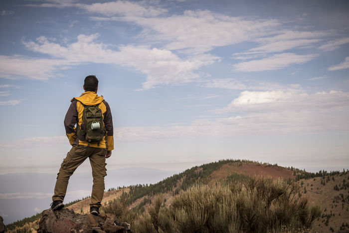 山頂で景色を見ている男性の写真