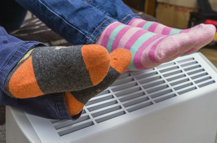 ファンヒーターで足を温めている様子