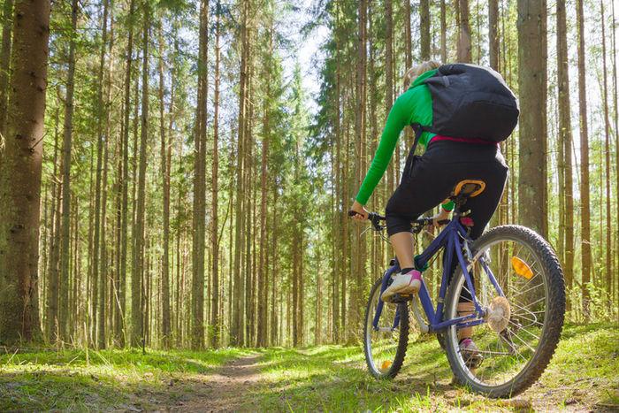 リュックを背負って山の中をサイクリングしている女性の写真