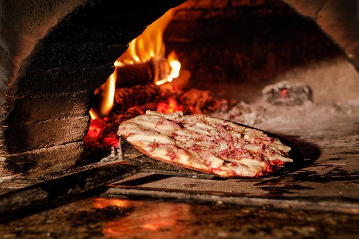 石窯でピザを焼いている様子の写真