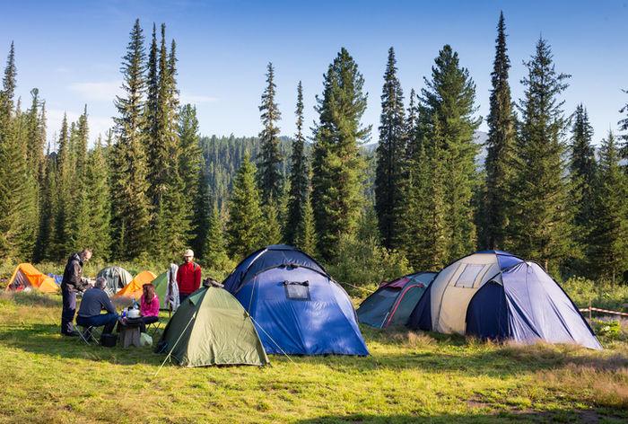山でテント貼ってキャンプをしている人たちの写真