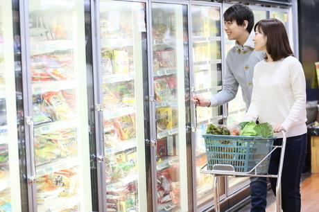 スーパーで男女が冷凍食品を見ている